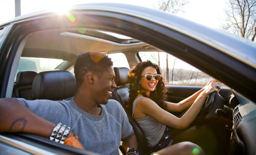 happy couple after learning ways to save money on car insurance
